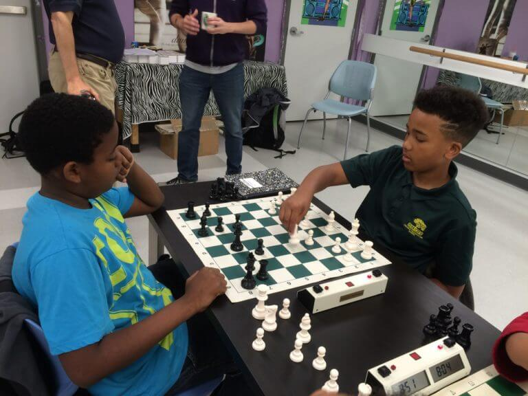 two achievement first students playing chess