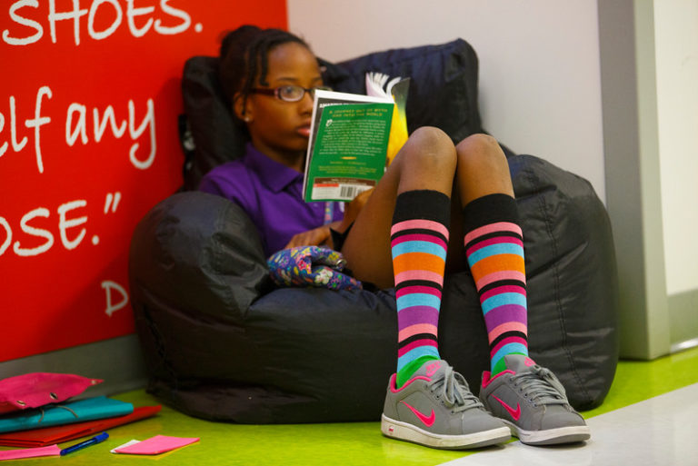 Young, female African American student with colorful socks sitting on a bean bag chair.