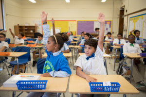 Students raise their hands in the classroom
