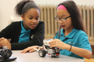 Two students work on a robotics project.