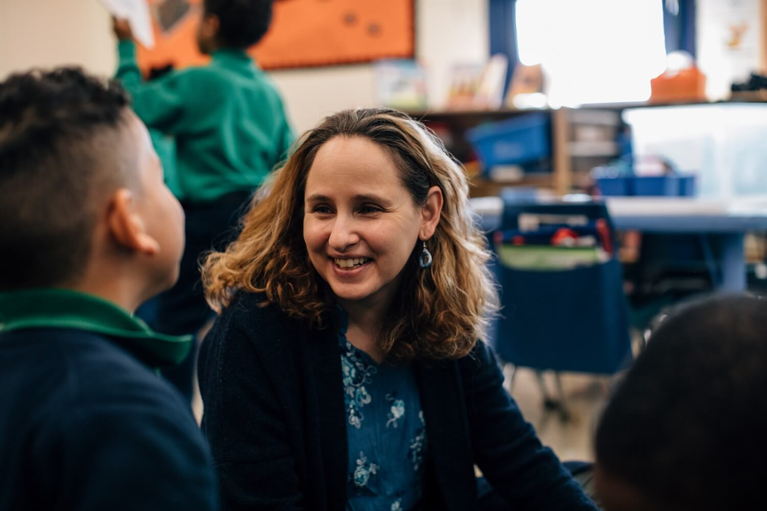 A teacher smiles at her students.