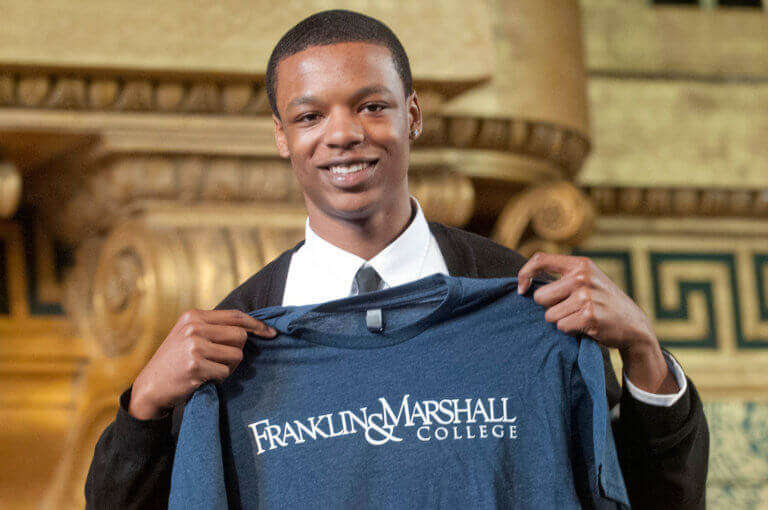 Tubyez holds up his college shirt for Franklin & Marshall