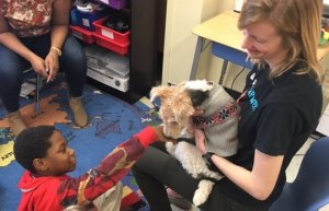 A student and teacher with a therapy dog