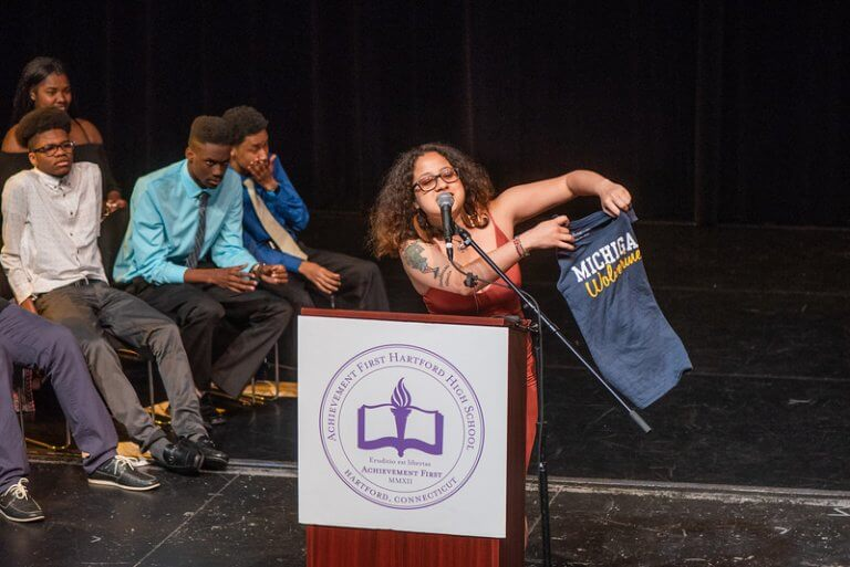 Thalía speaking at a podium holding up a t-shirt from the University of Michigan