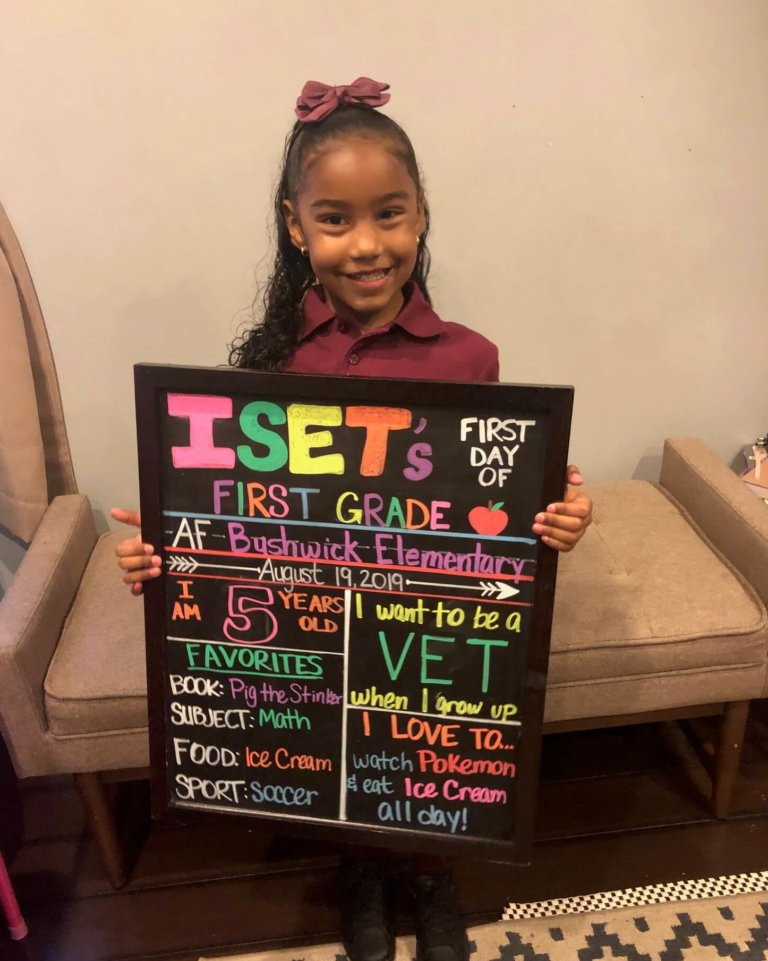 Iset holding up a blackboard with her name