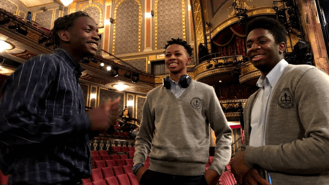 Three students standing together in a theater