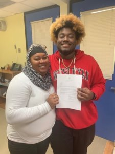 Darius and his mom holding a college acceptance