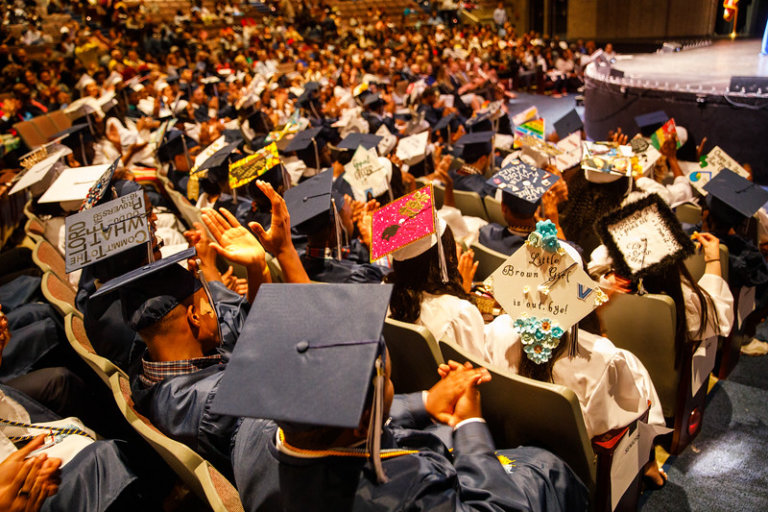 Students wearing caps and gowns in an auditorium